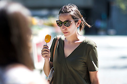© Licensed to London News Pictures. 02/08/2018. London, UK. A woman eating an ice cream while walking through Paddington Basin in London. Another heatwave is expected to hit parts of the UK with record temperatures expected in parts of Europe. Photo credit: Ben Cawthra/LNP