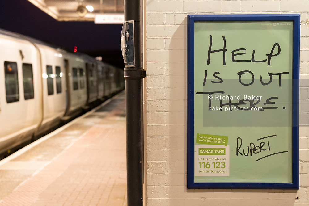 A train is stopped at Loughborough Junction railway station where a Samaritan's poster urges those with mental health issues, or even thoughts of suicide, to seek help from the registered charity aimed at providing emotional support to anyone in emotional distress, struggling to cope, or at risk of suicide throughout the United Kingdom and Ireland, often through their telephone helpline, on 26th February 2021, in London, England.