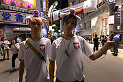 Two Japanese men dressed in the uniform of the Polish team join soccer fans celebrate the Japan National Team qualifying for the next round of the 2018 World Cup in Russia. Japan lost to Poland  0-1 but managed to move to the next stage on points. Thousands of younger fans gathered at Tokyo's iconic Shibuya crossing to enjoy the moment with police controlling the crowds