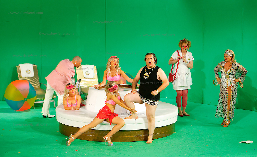Picture shows : Tiziano Bracci as Mustafa (centre) with bunny girls. Paul Carey Jones as Haly (pink jacket). Julia Riley as Zulma (with red bag) and Mary O'Sullivan as Elvira (far right)..Picture  ©  Drew Farrell Tel : 07721 -735041..A new Scottish Opera production of  Rossini's 'The Italian Girl in Algiers' opens at The Theatre Royal Glasgow on Wednesday 21st October 2009..(Soap) opera as you've never seen it before..Tonight on Algiers.....Colin McColl's cheeky take on Rossini's comic opera is a riot of bunny girls, beach balls, and small screen heroes with big screen egos. Set in a TV studio during the filming of popular Latino soap, Algiers, the show pits Rossini's typically playful and lyrical music against the shoreline shenanigans of cast and crew. You'd think the scandal would be confined to the outrageous storylines, but there's as much action off set as there is on.....Italian bass Tiziano Bracci makes his UK debut in the role of Mustafa. Scottish mezzo-soprano Karen Cargill, who the Guardian called a 'bright star' for her performance as Rosina in Scottish Opera's 2007 production of The Barber of Seville, sings Isabella..Cast .Mustafa...Tiziano Bracci.Isabella..Karen Cargill.Lindoro...Thomas Walker.Elvira...Mary O'Sullivan.Zulma...Julia Riley.Haly...Paul Carey Jones.Taddeo...Adrian Powter..Conductors.Wyn Davies.Derek Clarke (Nov 14)..Director by Colin McColl.Set and Lighting Designer by Tony Rabbit.Costume Designer by Nic Smillie..New co-production with New Zealand Opera.Production supported by.The Scottish Opera Syndicate.Sung in Italian with English supertitles..Performances.Theatre Royal, Glasgow - October 21, 25,29,31..Eden Court, Inverness - November 7. .His Majesty's Theatre, Aberdeen  - November 14..Festival Theatre,Edinburgh - November 21, 25, 27 ...Note to Editors:  This image is free to be used editorially in the promotion of Scottish Opera. Without prejudice ALL other licences without prior consent will be deemed a breach of copyright under t