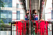 """Environmental Activist group Extinction Rebellion activists sit on the doors of the bank Standard Chartered, which has been covered in red paint during an Extinction Rebellion climate change protest in the city of London on Friday, 27 Aug 2021. This is their fifth day of an ongoing two-week disruption protest campaign """"The Impossible Rebellion"""". (VX Photo/ Vudi Xhymshiti)"""