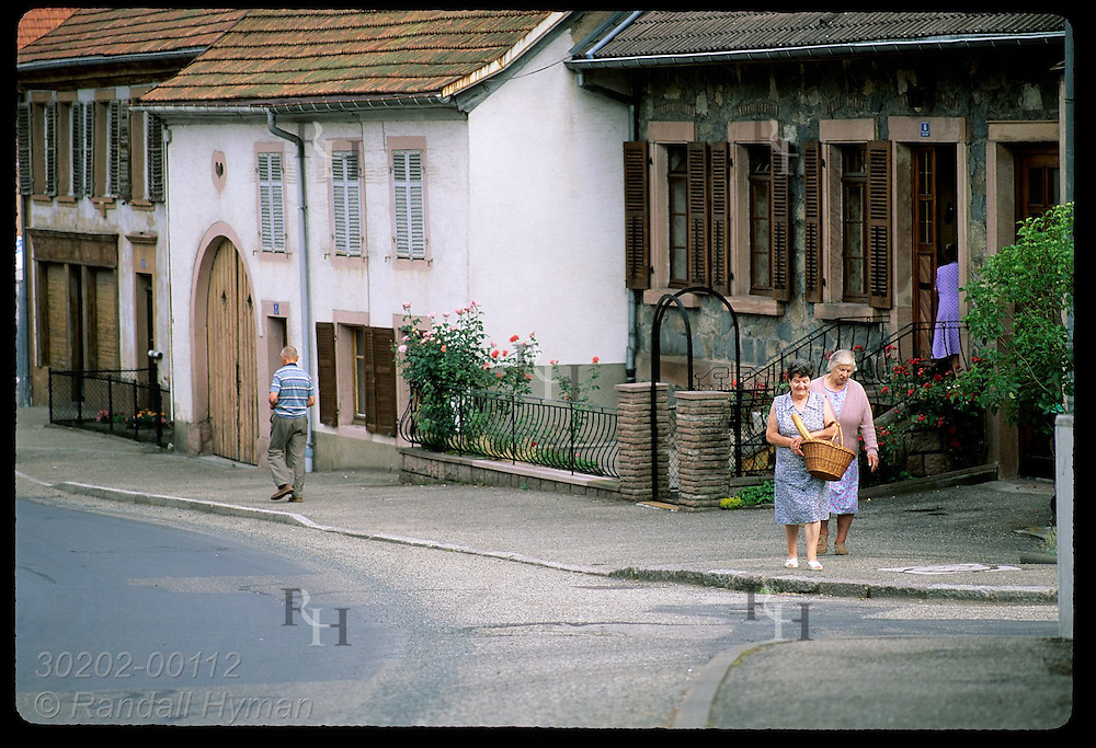 Woman with baguette chats with friend as they walk up street in town of Colroy-la-Roche. France
