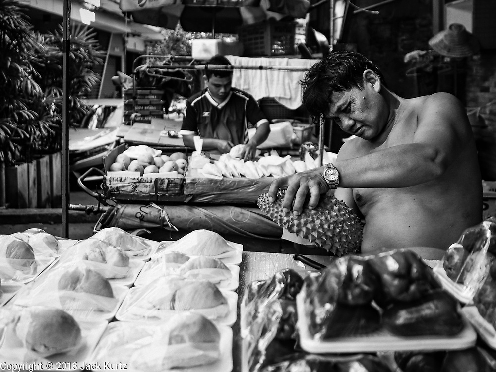17 DECEMBER 2018 - BANGKOK, THAILAND: Men cut up durian to sell in the morning market in a working class neighborhood about one kilometer from Siam Paragon, an exclusive mall in central Bangkok. According to Credit Suisse Global Wealth Databook 2018, which surveyed 40 countries, Thailand has the highest rate of income inequality in the world. In 2016, Thailand was third, behind Russia and India. In 2016, the 1% richest Thais (about 500,000 people) owned 58.0% of the Thailand's wealth. In 2018, they controlled 66.9%. In Russia, those numbers went from 78% in 2016, down to 57.1% in 2018. The Thai government disagreed with the report and said the report didn't take government anti-poverty programs into account and that Thailand was held to an unfair standard because most of the other countries in the report are developed countries in the Organisation for Economic Co-operation and Development.  PHOTO BY JACK KURTZ