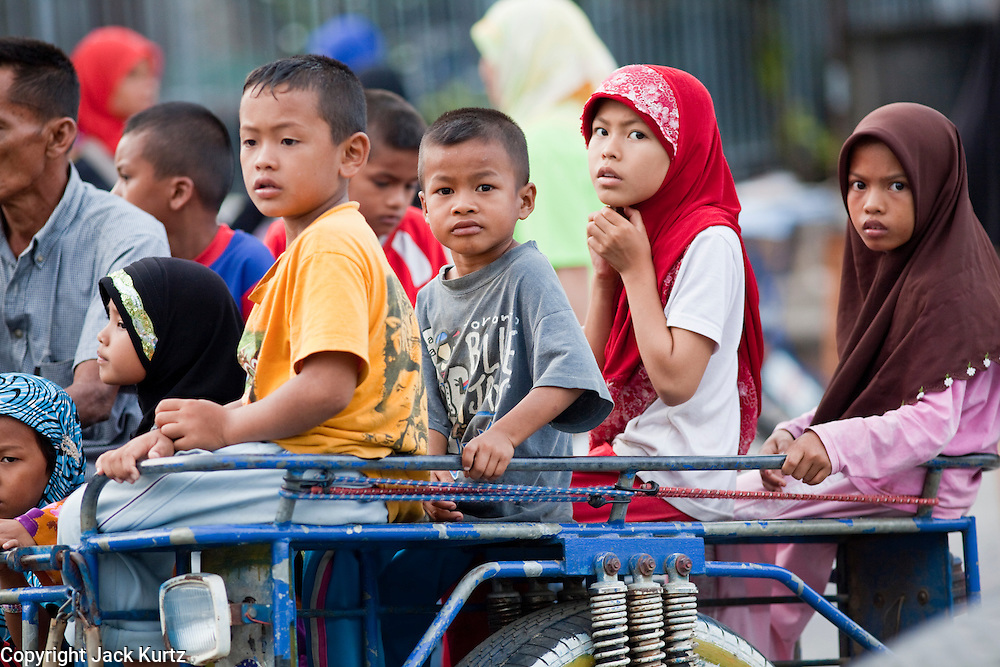 """Sept. 24, 2009 -- PATTANI, THAILAND:  Muslim children on a motorized trishaw in Pattani, Thailand. Thailand's three southern most provinces; Yala, Pattani and Narathiwat are often called """"restive"""" and a decades long Muslim insurgency has gained traction recently. Nearly 4,000 people have been killed since 2004. The three southern provinces are under emergency control and there are more than 60,000 Thai military, police and paramilitary militia forces trying to keep the peace battling insurgents who favor car bombs and assassination.   Photo by Jack Kurtz / ZUMA Press"""
