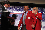 30 May 2012: 2012 Inductee Tony DiCicco (center) is helped into his red jacked by Hall of Famer Hank Steinbrecher as his presenter and son Anthony DiCicco (left) watches. The 2012 National Soccer Hall of Fame Induction Ceremony was held at Fedex Field in Landover, Maryland before a men's international friendly soccer match between the United States and Brazil.