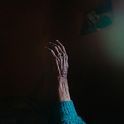 Detail of Radhika's hand, as she slowly turns around in her bed.