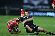 Paul Asquith of the Scarlets (l) is tackled by Kieron Fonotia of the Ospreys. Guinness Pro14 rugby match, Ospreys v Scarlets at the Liberty Stadium in Swansea, South Wales on Saturday 7th October 2017.<br /> pic by Andrew Orchard, Andrew Orchard sports photography.