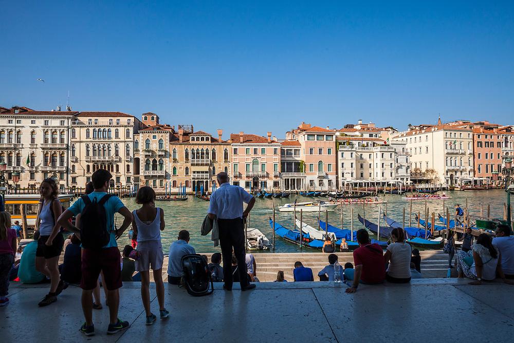 Tourists resting in the shady steps of Basilica di Santa Maria della Salute in Venice, Italy.