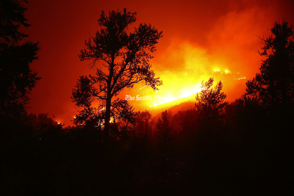Flames blanket the hillsides on Twisp River Road just outside of the town of Twisp, Wash. early in the morning Thursday, Aug. 20, 2015. Fire crews worked to contain the Twisp River Fire throughout the night.<br /> <br /> Erika Schultz / The Seattle Times