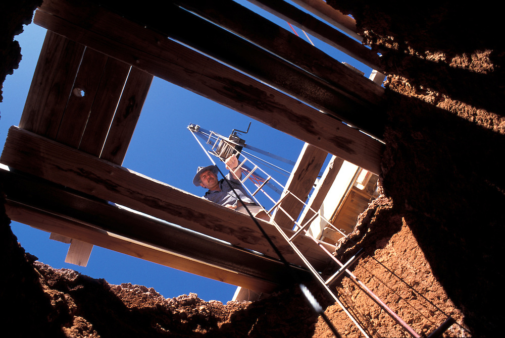 Australia, South Australia, (MR) Kary Aberhart hauls miner up 100' deep opal mine shaft in Coober Pedy.