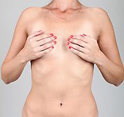 Naked woman covers her breasts with her hands