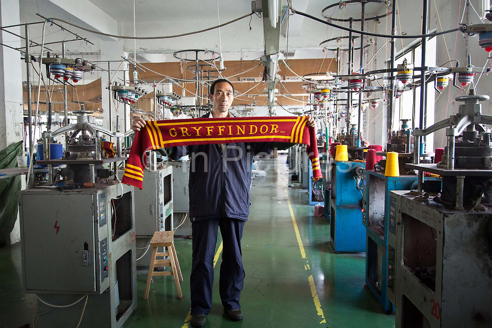 Line worker Wu Xianpin holds up a Harry Potter Gryffindor scarf at the Yiwu Wells Knitting Products Co., Ltd factory in Yiwu, Zhejiang Province, China on 06 March  2013. The city of Yiwu is known as one of China's largest trading centers for small merchandise and light industry, drawing buyers from around the world. Uncertain global demand, a stronger yuan currency and rising labour costs have taken their toll on Chinese exporters, but analysts believe sales could pick up modestly in 2014 due to improved demand from the United States and Europe.