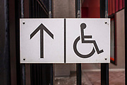 Disabled access sign outside the British Library in London, United Kingdom.  The sign has been modified from the International Symbol of Access designed in 1968. The symbol is often seen where access has been improved, particularly for wheelchair users, but also for other disability issues.  Frequently, the symbol denotes the removal of environmental barriers, such as steps, to help also older people, parents with baby carriages, and travelers.  This sign has an arrow to the left.