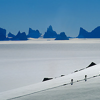 Expedition members ski near the Fenris Mountains in Queen Maud Land, Antarctica. Mount Ulvetanna is the large peak in the left background.