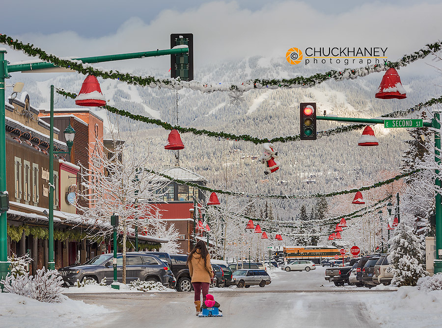 A mother takes infant for a sled ride down Central Avenure in Whitefish, Montana, USA