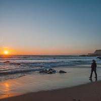 A woman walks along the wave front during sunset at Panther Beach, north of Santa Cruz, California.