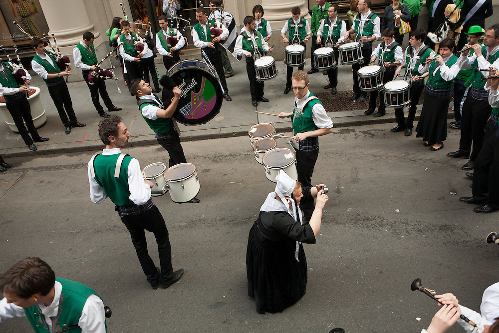 A woman from the Breton group Bagad Plougastell takes a photo as the band warms up before the parade.
