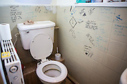Graffiti on the walls of a family toilet in the bathroom of a council house on an estate in Leyland, Lancashire.