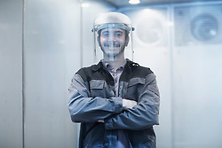 Portrait of a young male engineer wearing helmet in technology space and smiling, Freiburg Im Breisgau, Baden-Wuerttemberg, Germany