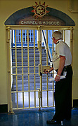 A prison officer locks the security gate to the prison chapel and mosque. HMP Wandsworth, London, United Kingdom.