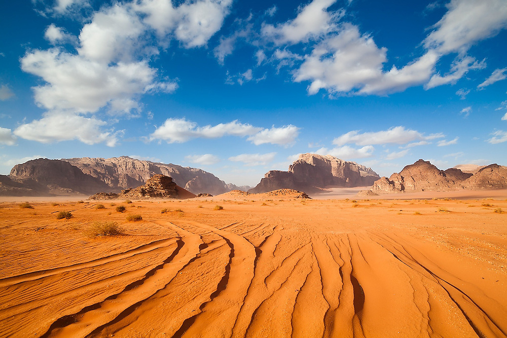 Jeep tracks cut through the red sand desert of Wadi Rum, Jordan
