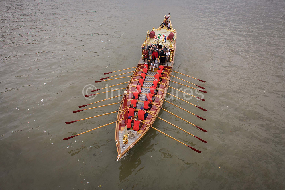 The royal rowbarge Gloriana is rowed on the River Thames on the occasion of celebrating the Queen's record of years as monarch. Passing beneath Westminster Bridge, the vessel is powered by members of its crew, the centrepiece of the flotilla of other boats and river-borne craft. Gloriana is a 94-foot-long (29 m) rowing barge. She is powered by 18 oarsmen and 2 electric inboard engines, and can carry an additional 34 passengers and crew. According to Lord Sterling, the design is inspired by Canaletto's London paintings of 18th-century barges. She was privately commissioned as a tribute to Queen Elizabeth II for her Diamond Jubilee, and was the lead vessel in the Thames Diamond Jubilee Pageant, a parade in 2012 of 670 boats on the Tideway of the River Thames.