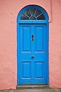 Bright  blue Georgian style door with fanlight above and pink lime mortar wall, in Ardmore Village, County Waterford, Ireland