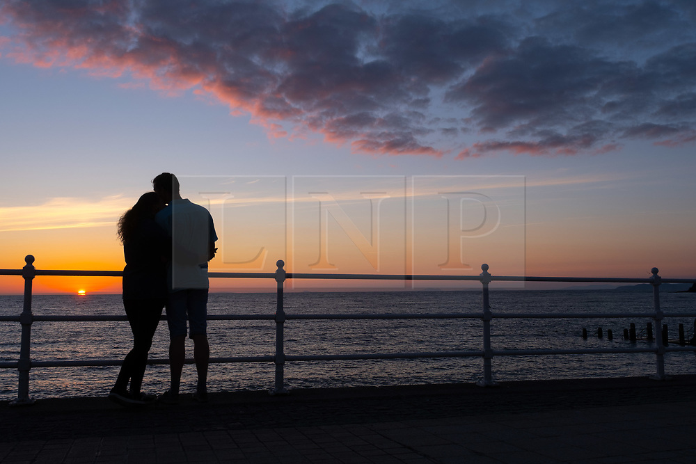 ©Licensed to London News Pictures<br /> 02/07/2019. Aberystwyth, UK.<br /> A couple embrace, silhouetted against the sky as they watch the glorious sunset in Aberystwyth on the Cardigan Bay coast, west Wales. Photo credit: Keith Morris/LNP