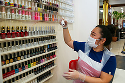 © Licensed to London News Pictures. 13/07/2020. London, UK. Nail beautician, HIEN THI THANH TRAN picks a nail polish for KRISTINA'S nails in her salon in North London. Nail technicians and nail salons across the UK closed on 23 March following the coronavirus lockdown. As COVID-19 lockdown restrictions are eased, nail salons reopen today. Nail technicians and their clients are required to wear face coverings. Photo credit: Dinendra Haria/LNP