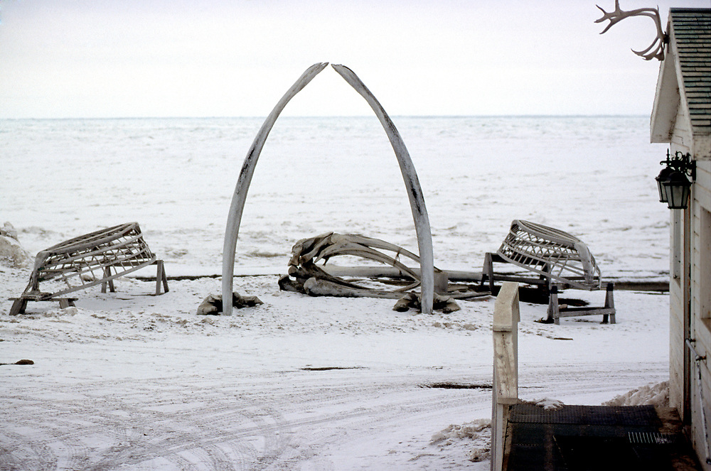 Bowhead whale jaw bones and umiaq frames by Brower's Cafe, nowadays a restaurant and in the old times it was Charles Brower's Trading Post. Charles Brower was a whaler from New York that came to Barrow for whaling. He the first white man to be established in Barrow and marry a native woman. Today the Brower family is numerous.<br /> <br /> May 14, 19:52