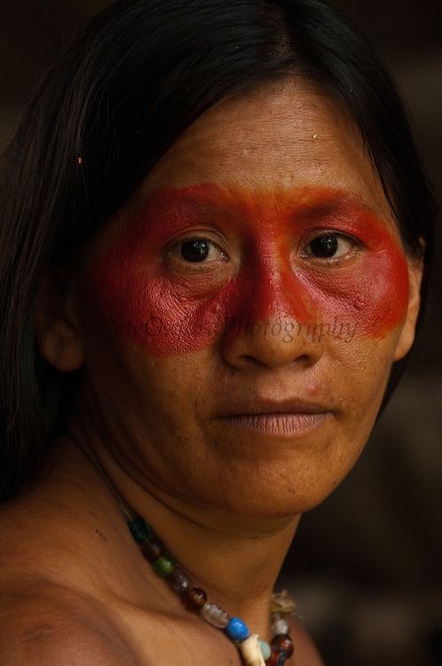 Huaorani Indian, Ewa Kemperi withbtraditional Huaorani mask face paint from the Achiote fruit.<br /> Bameno Community. Yasuni National Park.<br /> Amazon rainforest, ECUADOR.  South America<br /> This Indian tribe were basically uncontacted until 1956 when missionaries from the Summer Institute of Linguistics made contact with them. However there are still some groups from the tribe that remain uncontacted.  They are known as the Tagaeri & Taromenane. Traditionally these Indians were very hostile and killed many people who tried to enter into their territory. Their territory is in the Yasuni National Park which is now also being exploited for oil.