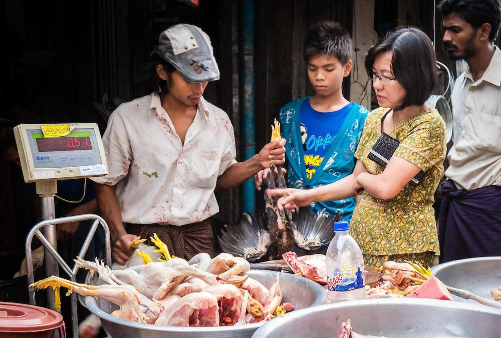 YANGON, MYANMAR - CIRCA DECEMBER 2013: Vendor selling chicken in street market of Yangon.