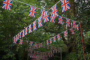 Hundreds of union jack flag bunting stretches back downhill through woods towards the local station during the annual Royal Ascot horseracing festival in Berkshire, England. Royal Ascot is one of Europe's most famous race meetings, and dates back to 1711. Queen Elizabeth and various members of the British Royal Family attend. Held every June, it's one of the main dates on the English sporting calendar and summer social season. Over 300,000 people make the annual visit to Berkshire during Royal Ascot week, making this Europe's best-attended race meeting with over £3m prize money to be won.