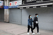 Chinese couple wearing face masks pass closed down souvenir tourist shops at Piccadilly, which is eerily quiet and silent on empty streets as lockdown continues and people observe the stay at home message in the capital on 12th May 2020 in London, England, United Kingdom. Coronavirus or Covid-19 is a new respiratory illness that has not previously been seen in humans. While much or Europe has been placed into lockdown, the UK government has now announced a slight relaxation of the stringent rules as part of their long term strategy, and in particular social distancing.