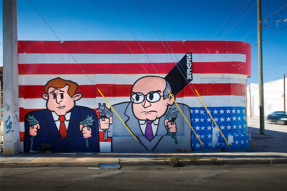 Gun-weilding caricatures of President George W. Bush and Vice-President Dick Cheney with a painted, upside-down American flag, photographed in Miami's Wynwood neighborhood in 2009.