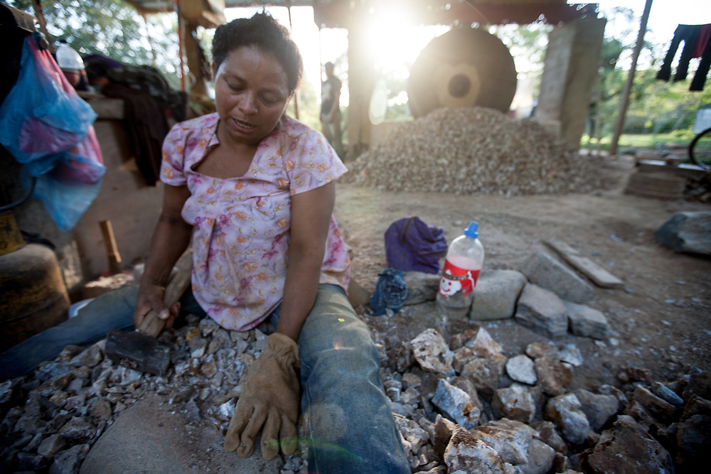 """A woman breaks gold ore or """"broza"""" with a hammer in a """"trapiche"""" style mill, also known as """"molino chileno"""". In artisanal gold mining in La Libertad, Chontales, Nicaragua, miners extract ore from open cast and underground mines, and crush and mill the ore to extract the gold with mercury."""