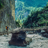 A trekker crosses a bridge over the monsoon-swollen Marsyandi River in the Manang Valley, north of Annapurna in Nepal.