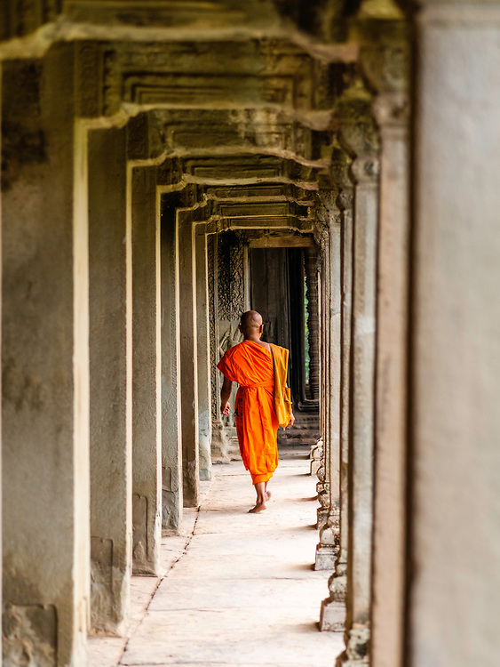 Monk walking along an outdoor hallway.  Angkor Wat Temple; Angkor Wat Archeological Park, Siem Reap, Cambodia.