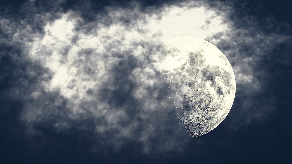 A spooky looking moon poking out of wispy clouds in the midnight sky