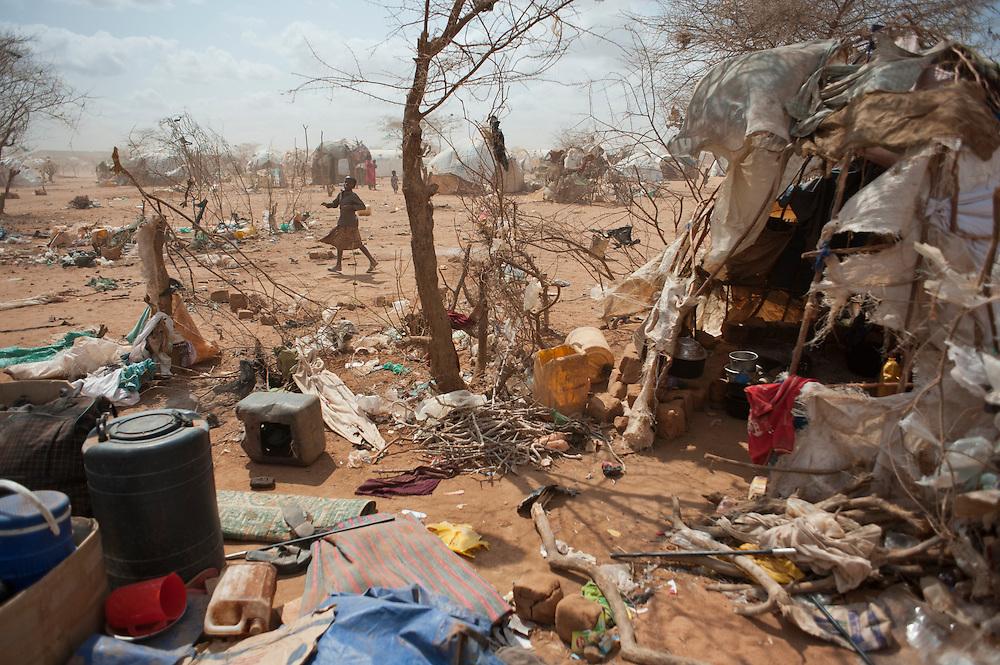 kenya, Dadaab, le 20-08-11 - camp de Dagahaley. Il accueille plus de 400 000 personnes, Dabaab est le plus grand camp de réfugiés au monde.  Ce sont pour la plupart des Somaliens (95%) ayant fuit la guerre et la famine, deux fléaux qui sévissent dans leur pays. Installés de manières anarchique à la périphérie du camp de Dagahaley, certains nouveaux arrivants survivaient dans des conditions extrêmement précaires. Un enfant joue dans un décor surréaliste. Les abris de fortune construits par les réfugiés de Dagahaley sont constitués uniquement de matériaux de récupération ramassés ça et là