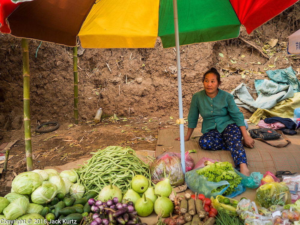 11 MARCH 2016 - LUANG PRABANG, LAOS:  A woman sells produce in the community of Chomphet, across the Mekong River from Luang Prabang. Laos is one of the poorest countries in Southeast Asia. Tourism and hydroelectric dams along the rivers that run through the country are driving the legal economy.      PHOTO BY JACK KURTZ