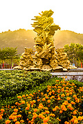 Sunrise on Lion Statue at attraction in South Vietnam. Golden light, backlit and flowers in the foreground frame this golden statue of a lion. Vertical, RAW to JPEG