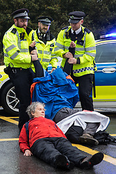 Colnbrook, UK. 27th September, 2021. Metropolitan Police officers remove an Insulate Britain climate activist from a slip road from the M25 at Junction 14 close to Heathrow airport which they had blocked as part of a campaign intended to push the UK government to make significant legislative change to start lowering emissions. The activists are demanding that the government immediately promises both to fully fund and ensure the insulation of all social housing in Britain by 2025 and to produce within four months a legally binding national plan to fully fund and ensure the full low-energy and low-carbon whole-house retrofit, with no externalised costs, of all homes in Britain by 2030.