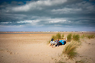 Scenic landscape of the wide beach sands at Holkham in north Norfolk, England with two ladies sunbathing in the sand dunes