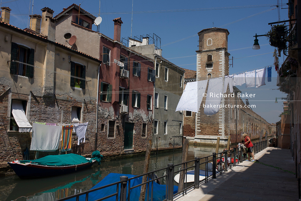 Washing hangs out over a narrow canal in the Castello district of Venice, Italy.