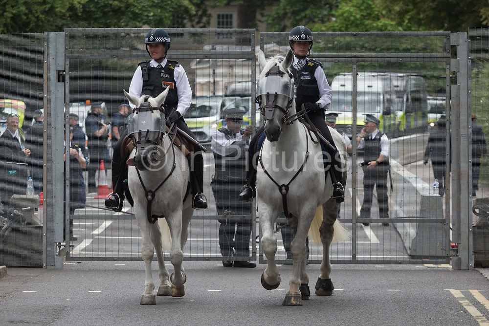 Mounted police officers leave the temporary perimeter fence encircling Winfield House, the official residence of the US Ambassador during the visit to the UK of US President, Donald Trump, on 12th July 2018, in Regents Park, London, England.