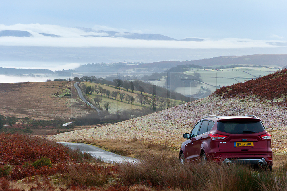 © Licensed to London News Pictures. 17/12/2019. Builth Wells, Powys, UK. A motorist negotiates a road through a frosty landscape on the moorland of the Mynydd Epynt range near Builth Wells in Powys, Wales, UK. after temperatures dropped  to below freezing last night. Photo credit: Graham M. Lawrence/LNP