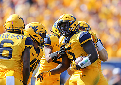 Oct 6, 2018; Morgantown, WV, USA; West Virginia Mountaineers defensive lineman Ezekiel Rose (5) celebrates with teammates after intercepting a pass during the first quarter against the Kansas Jayhawks at Mountaineer Field at Milan Puskar Stadium. Mandatory Credit: Ben Queen-USA TODAY Sports