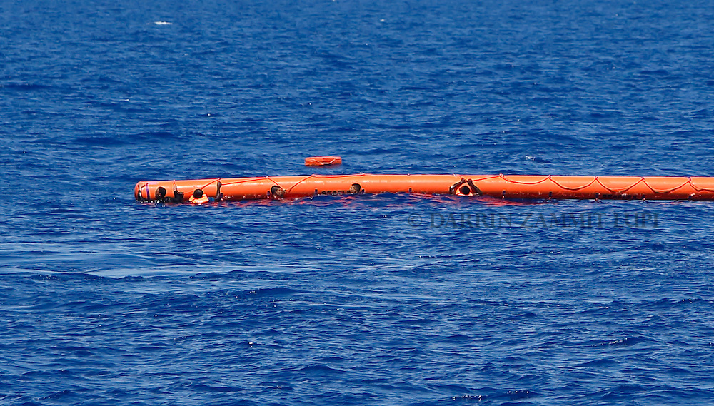 Migrants hang onto a flotation device during a rescue operation off the coast of Libya August 6, 2015.  An estimated 600 migrants on an overloaded wooden boat were rescued by the international non-governmental organisations Medecins san Frontiere (MSF) and the Migrant Offshore Aid Station (MOAS) without loss of life on Thursday afternoon, a day after more than 200 migrants are feared to have drowned in the latest Mediterranean boat tragedy after rescuers saved over 370 people from a capsized boat thought to be carrying 600.<br /> REUTERS/Darrin Zammit Lupi <br /> MALTA OUT. NO COMMERCIAL OR EDITORIAL SALES IN MALTA