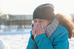 Girl sneezing in winter